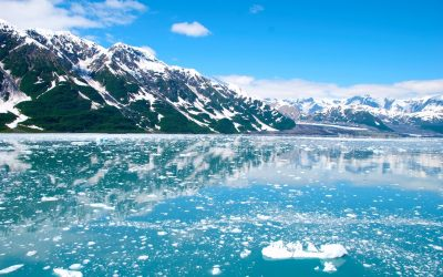 Cruise through icy water, surrounded by snowy mountains on an Alaskan cruise.